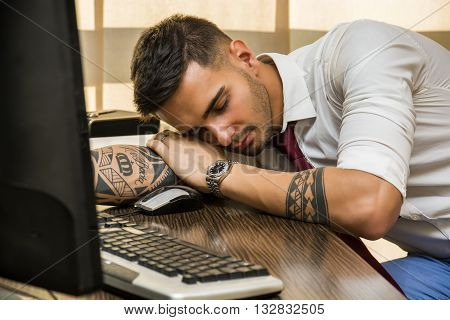 Overworked, tired young businessman sleeping on his desk in office, in front of computer