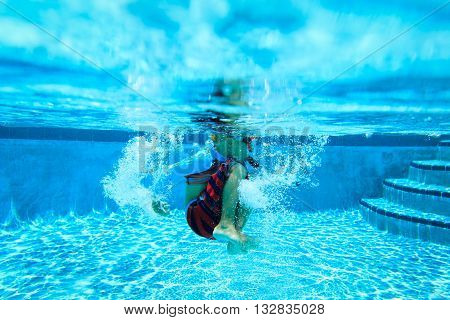 Underwater diving little boy with mask in swimming pool