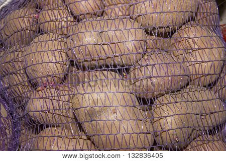 Potatoes Vegetables In A Grid, Mesh Bags Of Potatoes In A Truck, Fresh Raw Potatoes