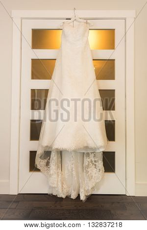 A wedding dress hangs on a bedroom closet door in warm bedroom light.
