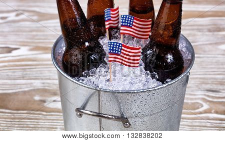 Miniature USA flags in bucket of ice with bottled beer. Fourth of July holiday concept for United States of America.