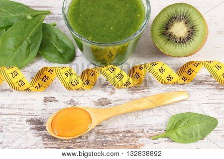Fresh ingredients and green nutritious cocktail from spinach with tape measure on old wooden background slimming and healthy nutrition