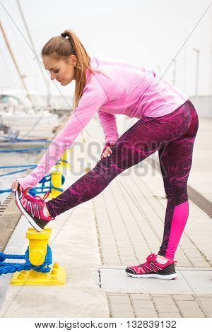 Slim sporty girl wearing sports wear and exercising or stretching in seaport healthy and active lifestyle on fresh air