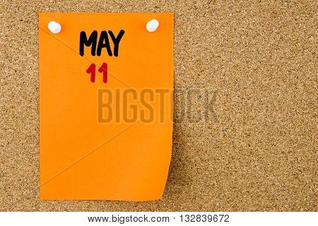 11 May Written On Orange Paper Note