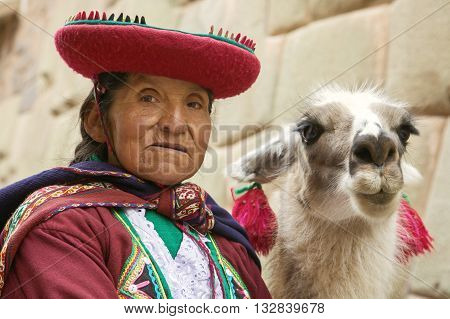 CUSCO PERU-NOVEMBER 26 2011: Portrait of old peruvian quechua woman in traditional clothes with llama in Cusco