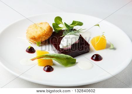 Beetroot terrine, goat cheese croquettes, horseradish sauce and dill cream on white dish.