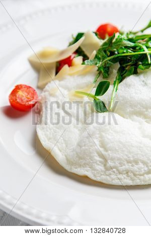 Fluffy Egg White Omelette with rukola, cheese and cherry tomatoes. White dish. Without yolk