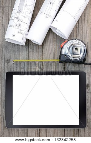 Digital Tablet With Architectural Blueprints Rolls And Tape Measure On Wooden Background
