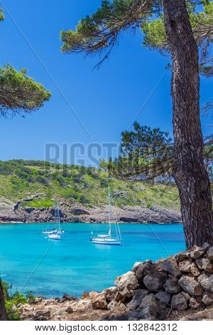 Beautiful Menorca island cove with yachts floating on turquoise water, Balearic islands, Spain
