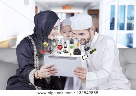 Happy middle eastern family using a digital tablet for shopping products online at home