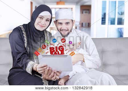 Happy middle eastern family holding a digital tablet with promo online shot at home