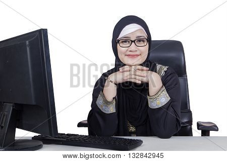 Photo of beautiful Arabic woman smiling at the camera while wearing headscarf with computer on the table