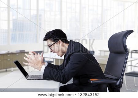 Portrait of young businessman yelling because he made a mistake on the laptop in office