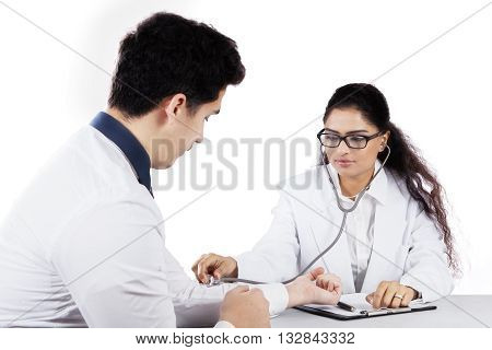 Female doctor using stethoscope for listening the heartbeat of male patient isolated on white background