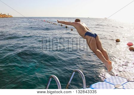 a man jumping from the pontoon bridge into the water sport leisure swimming jump into the water soft focus