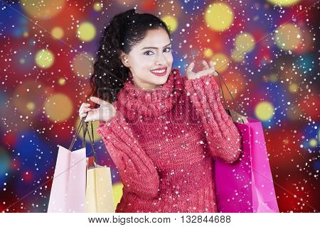 Beautiful indian woman holding shopping bags while wearing sweater with snowfall and bokeh background