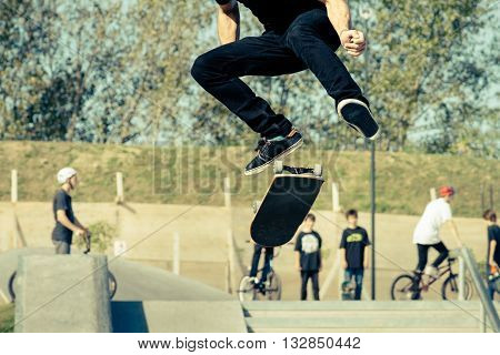 Young jumps with his skateboard at skatepark
