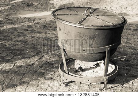 big ancient cauldron from iron or a boiler for cooking with a fire chamber for firewood and coals