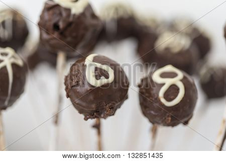 close up of chocolate cake pops on a stick