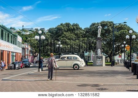 Wellington New Zealand - November 19 2014: Elderly man 1930s dressed and vintage motorcar on the Marine Parade in the art deco town of Napier New Zealand. Marine Parade is the main street in Napier.