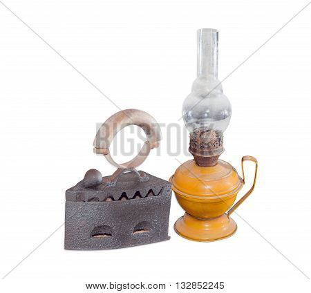 Old charcoal iron and old flat wick kerosene lamp on a light background