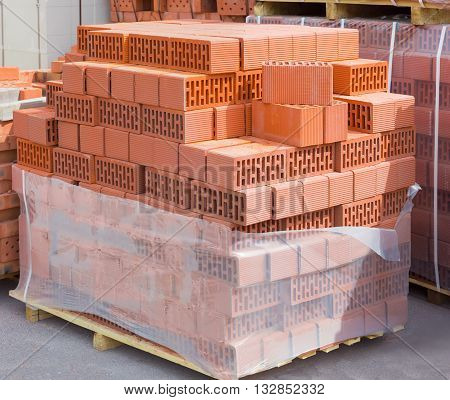 Wall blocks made from red porous ceramics with rectangular holes on a pallet on warehouse