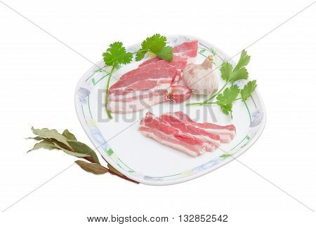 Several slices of uncooked streaky pork belly bacon garlic and sprigs of cilantro on a dish and laurel branch on a light background