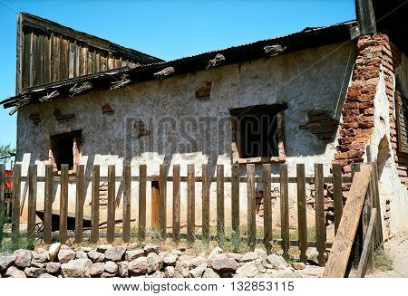 Old and damaged brick building with stucco and wooden fence