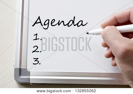 Human hand writing agenda on whiteboard .