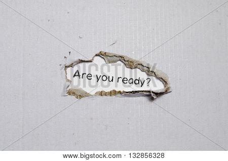 The word are you ready appearing behind torn paper.