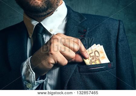 Businessman putting cash money in his pocket elegant businessperson with euro banknotes