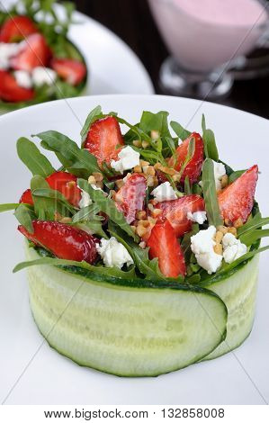 portion of strawberry salad with arugula and ricotta in cucumber