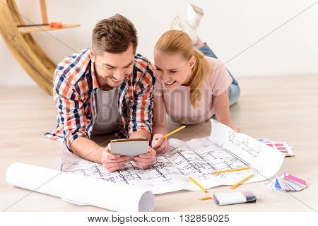Time for planning their new house. Happy young couple laying on the floor of their new apartment and looking at tablet