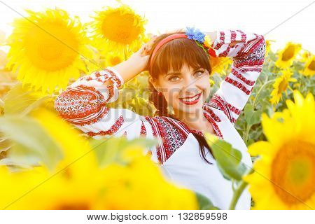 Beautiful smiling woman in national ukrainian blouse embrodery looking to camera on a sunflower field at sunset backlight.