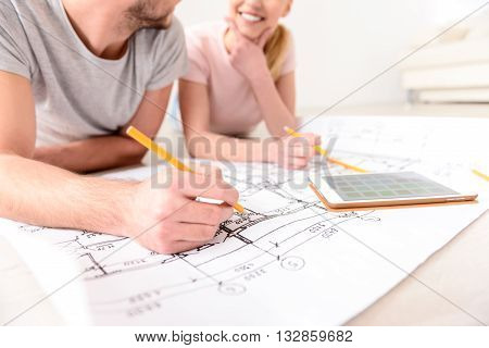 Close up of couple lying on floor of their new apartment and making marks on plan, using pencil