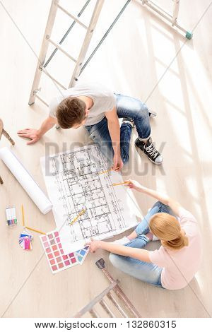 Large apartment-large plan. Top view of young family sitting on floor of their new apartment, considering plan and discussing ideas to repair.