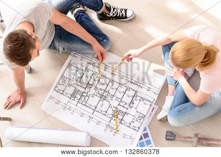 Long discussion. Top view of young couple sitting on floor discussing plan for new house, making pencil marks