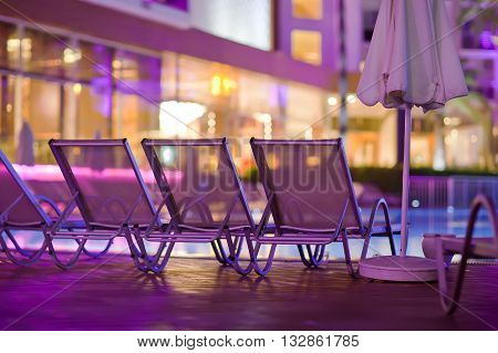 Chaise-longues by the pool in the evening.