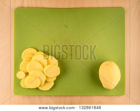 Whole and sliced peeled potatoe on green plastic board, simple food preparation illustration, vegetarian dieting, top view still life with center composition