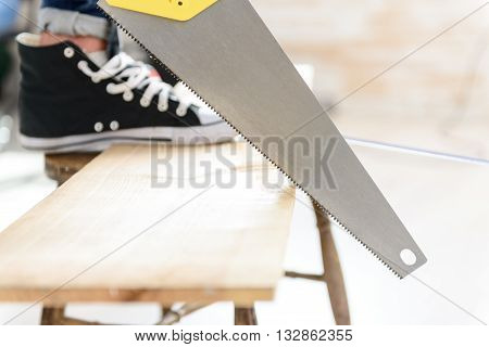 This taking steady hand. Close up of man sawing wooden board with handsaw, holding board by foot