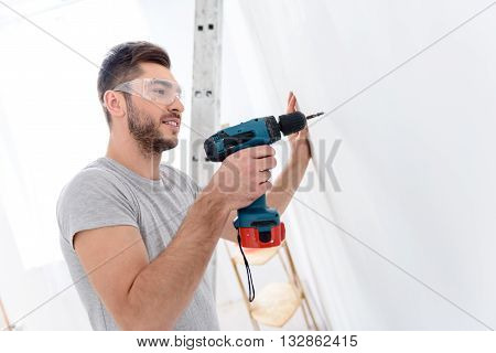 He handy to have around house. Portrait of smiling young man drilling hole into the wall in special protective glasses