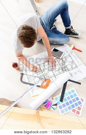 Planning new repair in my house. Top view of young guy siting on floor, making mark on architectural plan of his new home using pencil