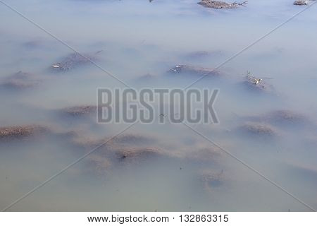 Agriculture plowed mud field under blurry water flood