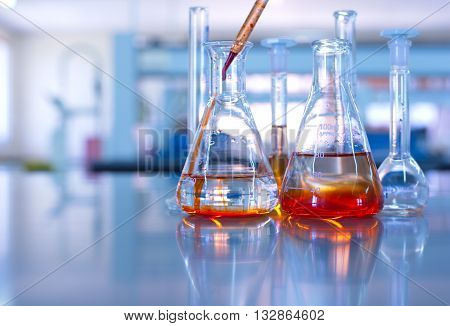 science laboratory glassware orange solution drop to flask