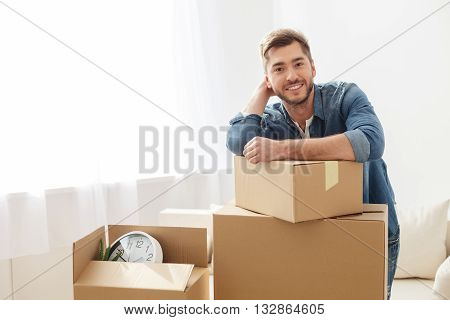 Feeling at home already. Smiling guy staying near cardboard box and having dreams of new repairs in his apartment