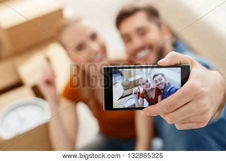 New home, new memories. Close up of shot of young couple moving into their new home and making selfie