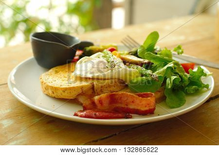 egg Benedict with bacon with green vegetable breakfast dish