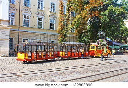 LVIV, UKRAINE - JULY 17, 2015: Sightseeing car train in the center of Lviv, Market square, Ukraine