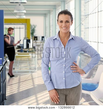 Happy middle-aged caucasian woman standing for portrait at colorful office.