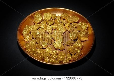 mound of gold in copper plate black background closeup
